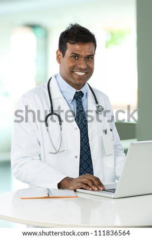 Male Indian doctor wearing a white coat, sitting at a desk working with his laptop.