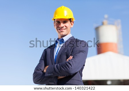 male industrial engineer in mining site with arms crossed