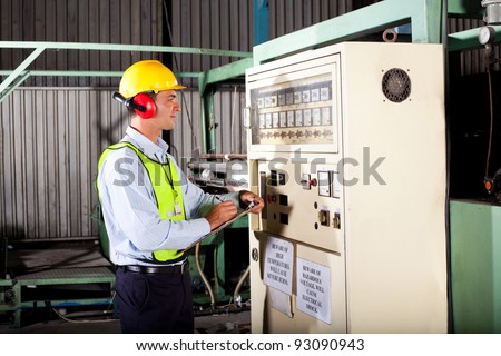 male industrial technician writing down machine temperature setting figures