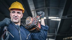 Male industrial worker in blue jumpsuit and hardhat carrying chain hoist on his back.