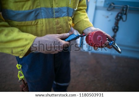 Male inspector hand testing by pulling red fall arrest self retracting absorber safety device equipment ensure its working correctly as daily inspection prior to used construction site Perth Australia