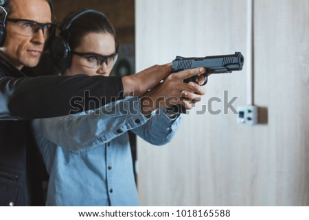 male instructor helping customer to shoot with gun in shooting range - Shutterstock ID 1018165588