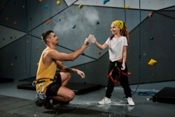 Male instructor teaching little girl, giving high five, applying white dust of magnesia, chalk on hands before climbing wall in bouldering center. Concept of sport and rock climbing. Horizontal shot