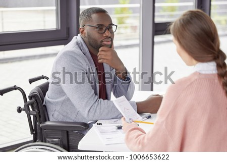 Male invalid involved in business activity, listens to female secretary who present annual report and new startup, suggests ways of canceling credit, believe in earning capacity and success. #1006653622