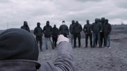 Male is talking to gang. Footage. Man gives speech to entire gang of gangsters in black jackets and masks. Criminal grouping with its own rules