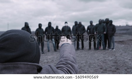 Photo of  Male is talking to gang. Footage. Man gives speech to entire gang of gangsters in black jackets and masks. Criminal grouping with its own rules