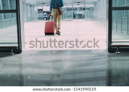 Male is walking in airport with luggage after arrival. Website banner #1541990519