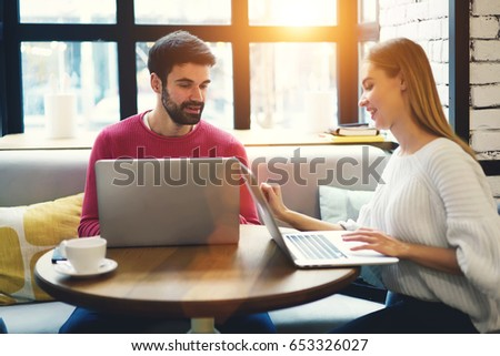 Male it professional explaining details of new program to female student on digital computer connecting to wireless 4G internet.Young woman with hipster guy working freelance together on laptop device