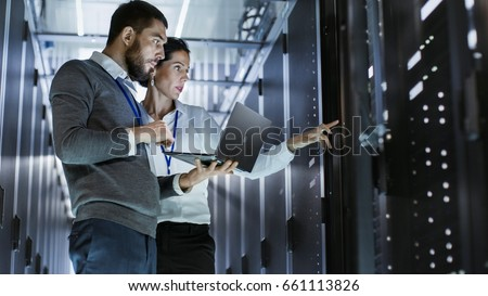 Male IT Specialist Holds Laptop and Discusses Work with Female Server Technician. They're Standing in Data Center, Rack Server Cabinet is Open. #661113826