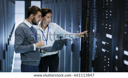 Male IT Specialist Holds Laptop and Discusses Work with Female Server Technician. They're Standing in Data Center, Rack Server Cabinet is Open.