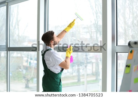 Male janitor cleaning window in office