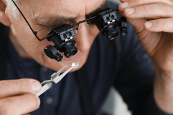 Male jeweler evaluating precious gemstone in workshop, closeup
