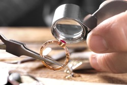 Male jeweler examining ruby ring in workshop, closeup view