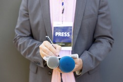 Male journalist at news conference or media event, holding microphone, writing notes. Journalism concept.