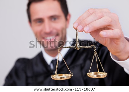 Male Judge Holding The Scale In Courtroom