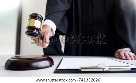 Male Judge lawyer In A Courtroom Striking The Gavel on sounding block. Foto stock ©