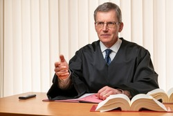 Male judge sitting at a desk speaking severely