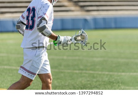 Male lacrosse player carrying a lacrosse ball in his stick. The player is wearing lacrosse pads and an all white uniform.