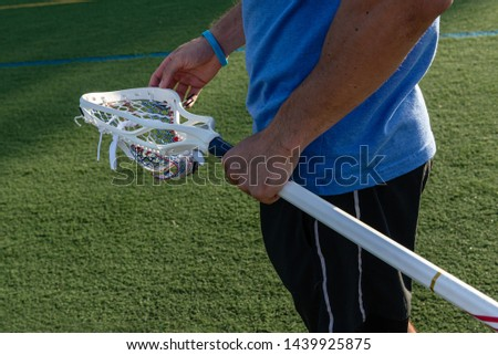 Male lacrosse player holding a men's lacrosse stick. The lacrosse mesh and lacrosse shaft are red, white, and blue.