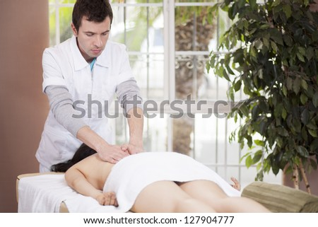 Male latin therapist giving a massage to a female customer