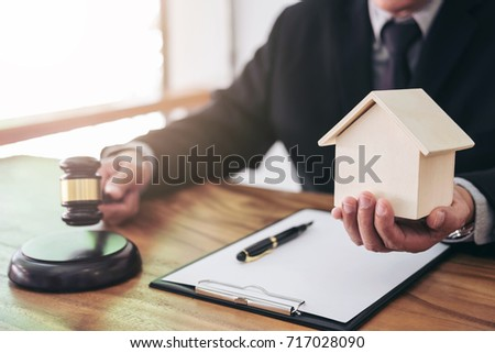 Male lawyer or judge hand's striking the gavel on sounding block, working at courtroom for decide home insurance, Law and justice concept, Settle a house dealing lawsuit.