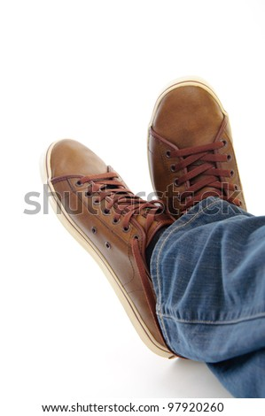 male legs in brown shoes sneakers and jeans lying down on the grownd isolated on white background