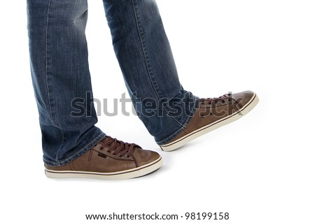 male legs in jeans and brown sneakers shoes make step isolated in white background