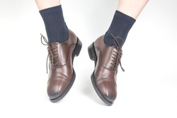 Male legs in socks and brown classic leather shoes on a white background