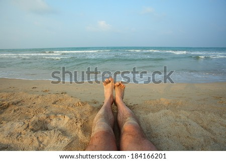 male legs on beach.Legs man lying on the beach shore of the Indian Ocean. Bay of Bengal Passikuda beach.