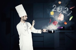 Male magician chef cooking on a saucepan with flying food ingredients and smoke shaped of numbers 2021 in the kitchen