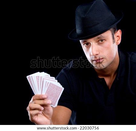 male magician holding cards in his hand - isolated over black