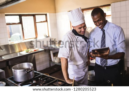 Male manager and chef using digital tablet in kitchen at hotel