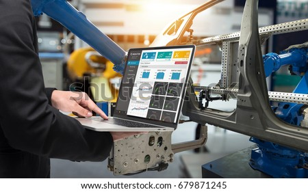Male manager hand laptop for check real time production monitoring system application in smart factory industrial. Automobile manufacturing production machine , robot arm. industry 4.0 concept.