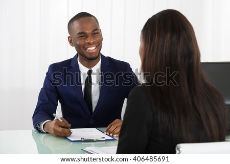 Male Manager Interviewing A Young Female Applicant In Office