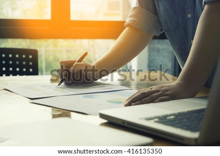 Male manager putting his ideas and writing business plan at workplace,man holding pens and papers, making notes in documents, on the table in office,vintage color,morning light ,selective focus. #416135350