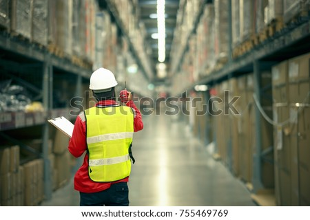 male manager using handheld in a large warehouse  worker checking delivering boxes. distribution center. logistics concept.