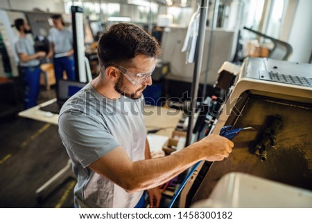 Male manual worker working with CNC machine in a factory.
