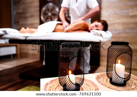 Male masseur doing massage rubbing oil on the back of a young beautiful girl. blurred background in the foreground candles #769631500