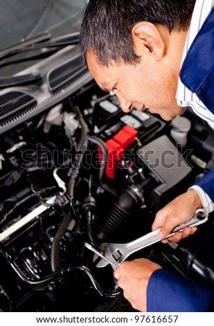 Male mechanic fixing an engine at a car garage