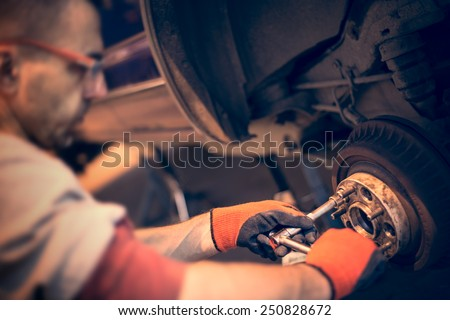 Male mechanic in gloves tightening the nuts using wrench. Mending, repair car in workshop.
