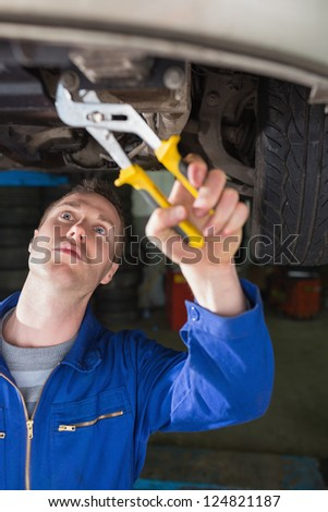 Male mechanic repairing car with adjustable pliers in garage