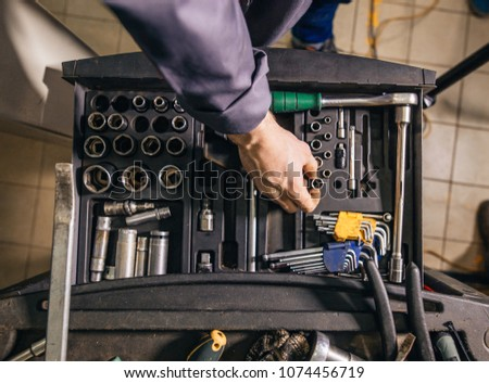 male Mechanic taking instruments from toolbox in repair garage