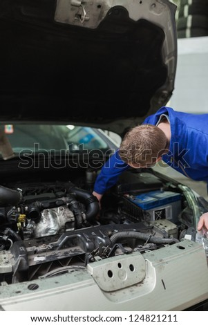 Male mechanic working under bonnet of car - stock photo