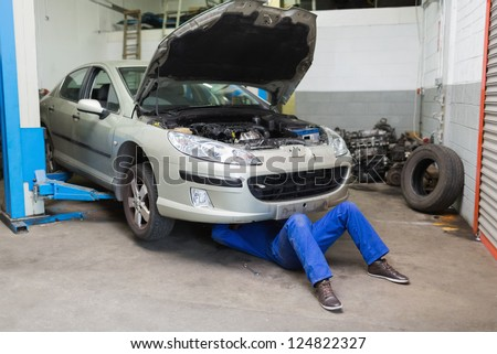 free photos male mechanic working under car at garage. Black Bedroom Furniture Sets. Home Design Ideas