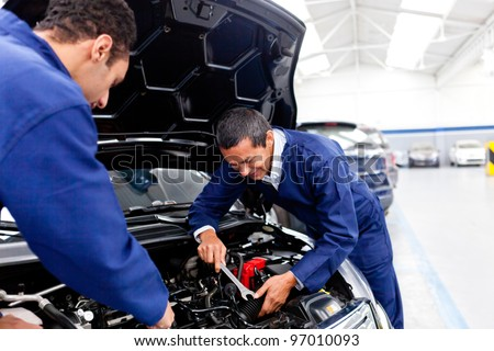 Male mechanics at the garage fixing a car - stock photo