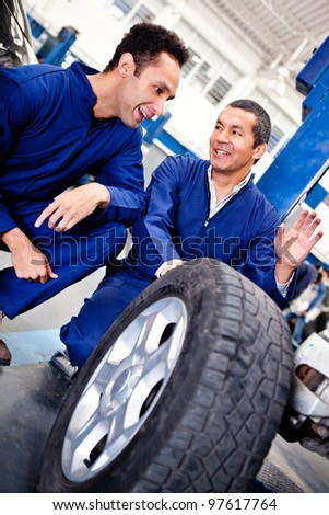 Male mechanics working as a team on car puncture