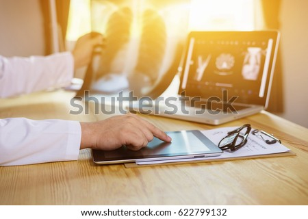 male medicine doctor explains to patient diagnosis pointing with tablets to x-ray picture. Patients listening carefully specialist recommendations. Medical care concept. Radiologist or traumatologist