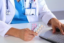 Male medicine doctor hands hold jar of pills and type something on laptop computer keyboard. Panacea life save, prescribing treatment, legal drug store, take stock, consumption statistics concept