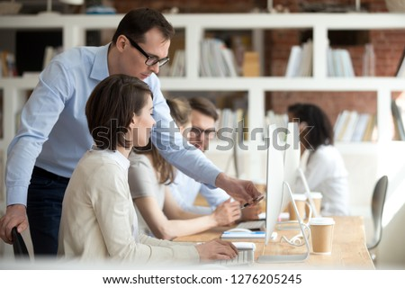 Male mentor supervisor ceo helping female employee explaining subordinate online project computer work in office, focused executive manager teach intern, team leader pointing on pc training coworker