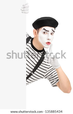 Male mime artist holding a blank panel and gesturing silence with a finger on his mouth, isolated on white background